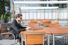 Hombre de negocios o trabajador en traje negro en la tabla y trabajo masculinos en el ordenador Fotos de archivo