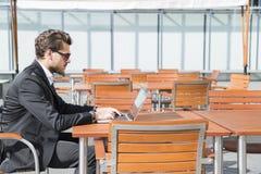 Hombre de negocios o trabajador en traje negro en la tabla y trabajo masculinos en el ordenador Imagenes de archivo
