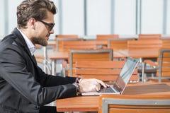 Hombre de negocios o trabajador en traje negro en la tabla y trabajo masculinos en el ordenador Foto de archivo
