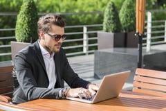 Hombre de negocios o trabajador en traje negro en la tabla y trabajo masculinos en el ordenador Fotos de archivo libres de regalías