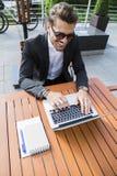 Hombre de negocios o trabajador en traje negro en la tabla y trabajo masculinos en el ordenador Imagen de archivo libre de regalías