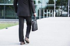 Hombre de negocios o trabajador que se coloca en traje cerca del edificio de oficinas Fotografía de archivo