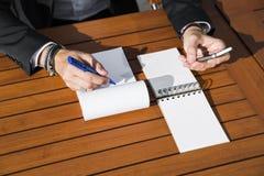 Hombre de negocios o trabajador de sexo masculino en traje negro en la tabla y la escritura en cuaderno Imagen de archivo libre de regalías