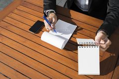 Hombre de negocios o trabajador de sexo masculino en traje negro en la tabla y la escritura en cuaderno Imágenes de archivo libres de regalías