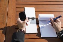 Hombre de negocios o trabajador de sexo masculino en traje negro en la tabla y la escritura en cuaderno Imagen de archivo