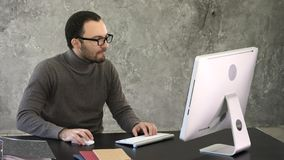 Hombre de negocios ocasional que trabaja en oficina, sentándose en el escritorio, pulsando en el teclado, mirando la pantalla de  foto de archivo