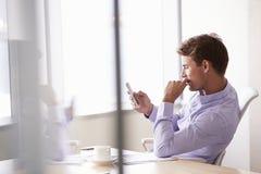 Hombre de negocios ocasional vestido Using Mobile Phone en oficina Fotos de archivo