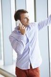 Hombre de negocios ocasional vestido Using Mobile Phone en oficina Imágenes de archivo libres de regalías