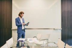 Hombre de negocios occidental subrayado usando una tableta aislada con el espacio en blanco Foto de archivo libre de regalías