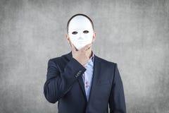 Hombre de negocios ocultado detrás de la máscara Fotografía de archivo