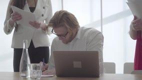 Hombre de negocios ocupado acertado del retrato en los vidrios que se sientan en una oficina cómoda ligera con netbook en la firm metrajes