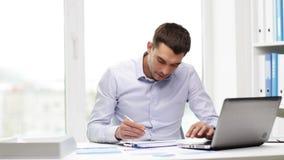 Hombre de negocios ocupado con el ordenador portátil y los papeles en oficina metrajes