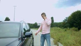 Hombre de negocios ocupado con el teléfono que consigue en el coche almacen de video