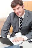 Hombre de negocios ocupado con la computadora portátil, el teléfono celular y la taza Imagenes de archivo