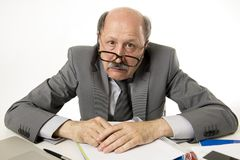 Hombre de negocios ocupado maduro mayor con la cabeza calva en su funcionamiento 60s subrayado y frustrado en el escritorio del o Imagen de archivo libre de regalías