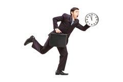 Hombre de negocios ocupado que se ejecuta con el reloj y la cartera de pared Imagen de archivo libre de regalías
