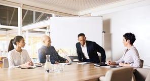 Hombre de negocios ocupado, sentándose en la tabla de la sala de reunión con otros miembros imagen de archivo libre de regalías