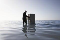 Hombre de negocios Opening Filing Cabinet en el mar fotos de archivo