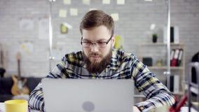 Hombre de negocios organizado productivo que inclina el trabajo de oficina detrás de acabado en el ordenador portátil, encargado  almacen de video