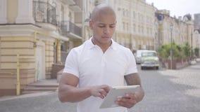Hombre de negocios de Oriente Medio calvo hermoso que mecanografía en la tableta tanding en la calle de la ciudad Concepto indepe metrajes