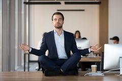 Hombre de negocios pacífico que medita con los ojos cerrados en el lugar de trabajo foto de archivo libre de regalías