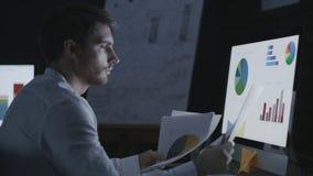 Hombre de negocios de pensamiento que mira cartas y gráficos financieros en oficina oscura almacen de video