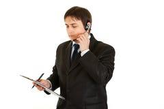 Hombre de negocios pensativo con el receptor de cabeza y el sujetapapeles Fotos de archivo libres de regalías