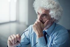 Hombre de negocios pensativo con la mano en la barbilla imagen de archivo