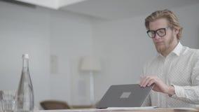 Hombre de negocios pensativo del retrato en los vidrios que se sientan en la tabla en una oficina cómoda ligera delante del netbo almacen de metraje de vídeo
