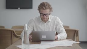 Hombre de negocios pensativo del retrato en los vidrios que se sientan en la tabla en una oficina c?moda ligera delante del netbo almacen de metraje de vídeo