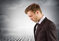 Hombre de negocios pensativo que mira abajo con laberinto en fondo Imágenes de archivo libres de regalías