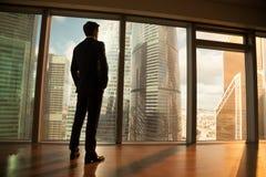 Hombre de negocios pensativo que mira fuera de ventana grande la ciudad de la puesta del sol foto de archivo libre de regalías