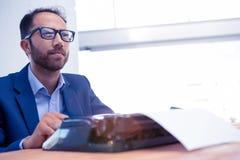 Hombre de negocios pensativo que parece ausente mientras que trabaja en la máquina de escribir Fotografía de archivo