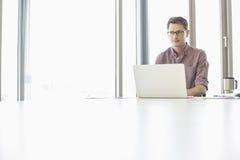 Hombre de negocios pensativo que parece ausente mientras que usa el ordenador portátil en el escritorio en oficina creativa imágenes de archivo libres de regalías