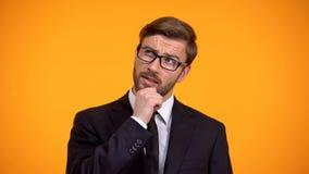 Hombre de negocios pensativo que piensa en las ideas para el comienzo para arriba, fondo anaranjado fotos de archivo