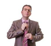 Hombre de negocios pensativo que pone su lazo en el fondo blanco Imagen de archivo