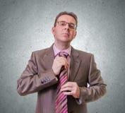 Hombre de negocios pensativo que pone su lazo en el fondo blanco Fotografía de archivo libre de regalías