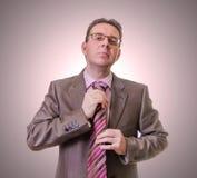 Hombre de negocios pensativo que pone su lazo en el fondo blanco Imagen de archivo libre de regalías