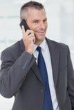 Hombre de negocios pensativo que presenta mientras que teniendo una llamada de teléfono imagenes de archivo
