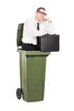 Hombre de negocios pensativo que se coloca dentro de un bote de basura Fotografía de archivo