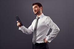 Hombre de negocios que sostiene la PC de la tableta y que mira para arriba Imágenes de archivo libres de regalías