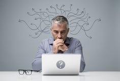 Hombre de negocios pensativo que trabaja con un ordenador portátil fotografía de archivo