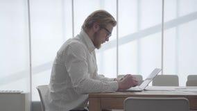 Hombre de negocios pensativo rubio hermoso del retrato en los vidrios que se sientan en la tabla en una oficina cómoda ligera del almacen de video
