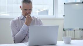Hombre de negocios pensativo Thinking y trabajo en el ordenador portátil foto de archivo