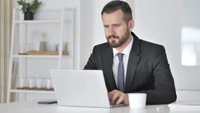 Hombre de negocios pensativo Thinking y trabajo en el ordenador portátil almacen de video