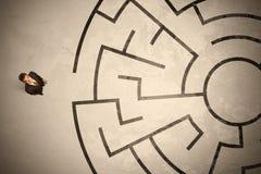 Hombre de negocios perdido que busca una manera en laberinto circular Imagen de archivo