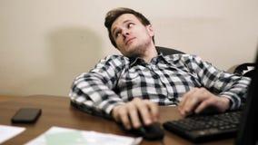 Hombre de negocios perezoso joven que se sienta en oficina almacen de metraje de vídeo