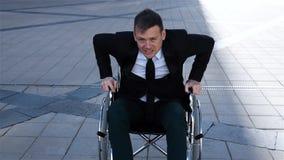 Hombre de negocios perjudicado capaz que intenta levantarse de la silla de ruedas almacen de metraje de vídeo
