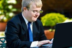 Hombre de negocios perjudicado joven que trabaja en el ordenador portátil Fotografía de archivo libre de regalías