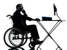 Hombre de negocios perjudicado que trabaja en silueta de la silla de ruedas en whe imagen de archivo